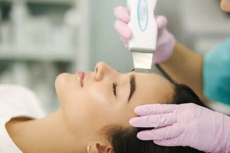 Close up of female face with soft skin. Woman at cosmetology clinic taking a beauty procedure for skin clining.