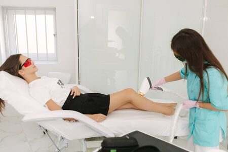 Young woman getting laser treatment on leg at spa. Laser epilation and cosmetology.