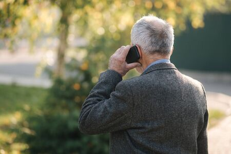 Back view of elderly man speak by the mobile phone outside