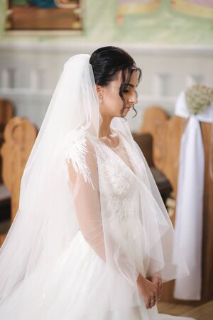Charming bride in the church on the wedding day Stock Photo
