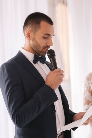 Handsome groom reading wedding vows and started crying. Groom have feeling of overwhelming love for bride
