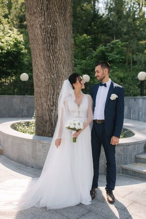 Beautiful bride with her handsome groom walking outside on theri wedding day. Happy newlyweds