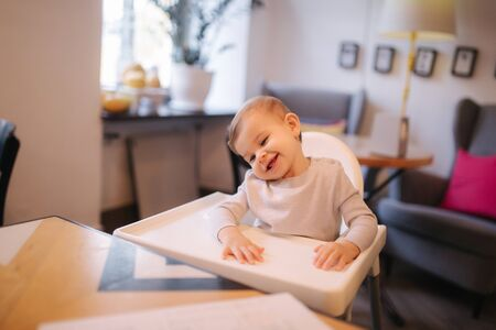 Portrait of adorable little girl on highchair. Baby laughing and play. Happy girl smile Stock Photo