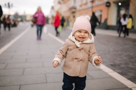 Portrait of baby girl in coat and hat laughing. Cute baby outside