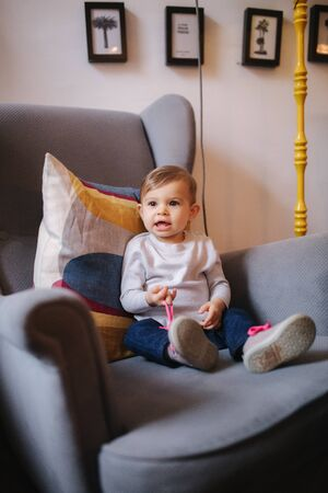 Cute baby girl sitting on big armchair and smile Stock Photo