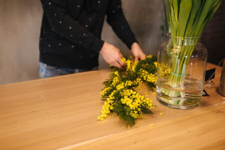 Man making flower bouquet. Spring yellow boquet with tulips Stock Photo