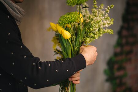 Flowers delivery shop. Florist creating order, making spring bouquet. Male make bouquet using yellow tulips.