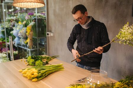 Man making flower bouquet. Spring yellow boquet with tulips.