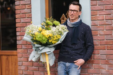 Stylish man in glasses hold bouquet of flower outside. Background of brick wall