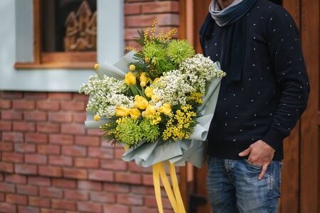 Handsome man in glasses hold bouquet of flower outside. Background of brick wall.
