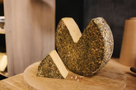 Big piece of cheese on wooden board.