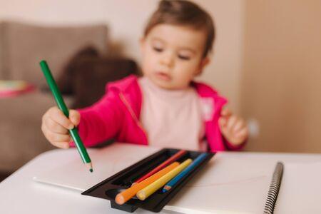 Glückliches Baby sitzt am Tisch und whirre etwas. Kleines Mädchen benutzt Bleistift zum Zeichnen auf weißem Papier zu Hause