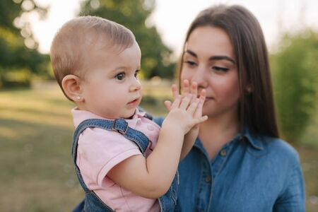 Cute baby on moms hands outside. Family in the park in summer. Denim style. Mom and daughter in jeans