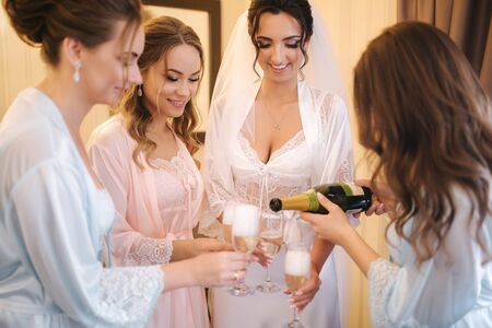Gorgeous bride with best bridesmaids drinking champagne in hotel. Morning of bride. Sexy bridesmaids in exciting negligee