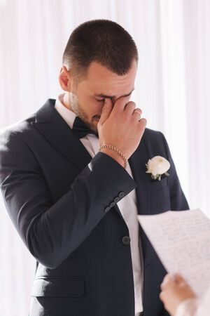 Handsome groom reading wedding vows and started crying. Groom have feeling of overwhelming love for bride.