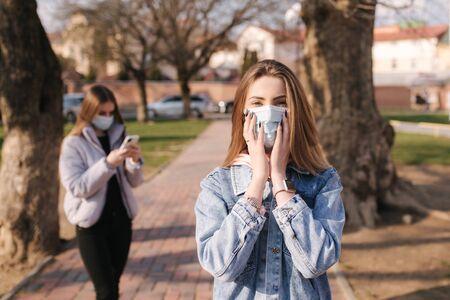 Girls in masks. Coronavirus theme. Women in the city walks during quarantine. Woman hut hands on face