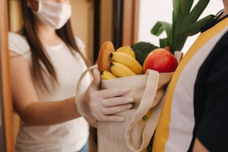 Delivery man in mask and gloves give fresh food to recipient and young woman customer. Stay home, Online shopping concept