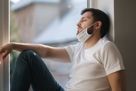 Young man sits on windowsill and pulled protective mask below on the chin and look s out the window. Alone at home in quarantine. Coronavirus theme. Stay at home Banco de Imagens
