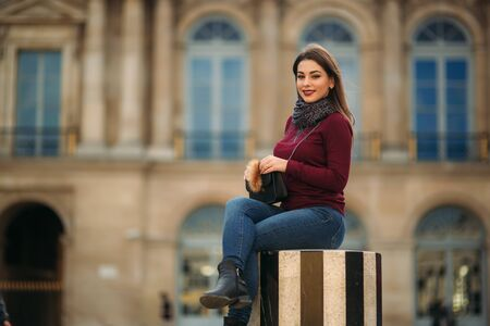 Attractive young womanl in burgundy blouse with a gray scarf sits on a striped dais. Happy woman in Paris