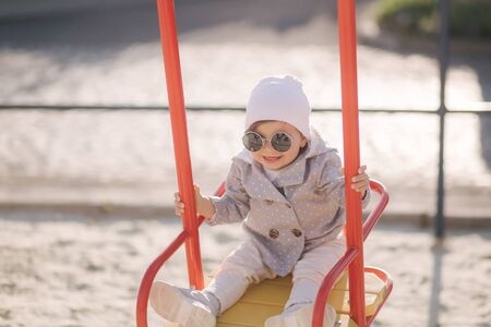 Adorable little girl on the swing set in playground. Happy little girl have fun. One and hulf year girl