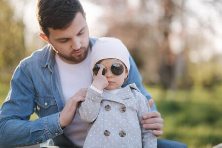 Dad put on sunglasses to his little daughter in suuny day