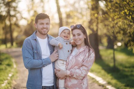 Portrait of happy family in the park. Father mother and litthe daughter. Adorable little with with mom and dad. Young family, Handsome dad and attractive young mom. Happy Mothers Day