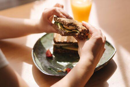 Woman hold in hands bitten sandwich. Rye toasted bread with avocado. Fresh orange juice Vegan food