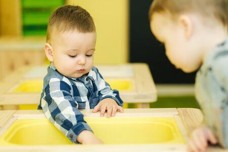 Gros plan sur des enfants qui apprennent à l'école maternelle. Garçon jouant avec un jouet en bois Banque d'images