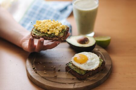 Woman hold toasted sandwich. Egg on avocado sandwich with whole grain bread on wooden board. Smoothie with spinach