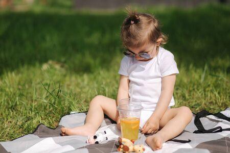Happy little kid sits outdoors on carpet and drink lemonade. Adorable little girl in white bodysuit Stockfoto