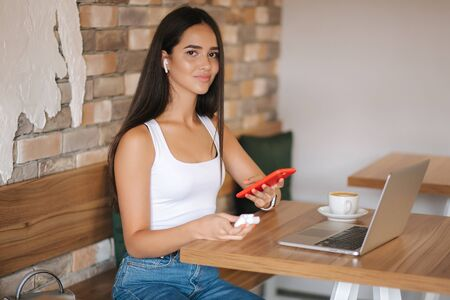 Attractive young girl use wireless headphones and working on laptop. Woman in white t-shirt and denim. Student study in cafe. Alone in cafe