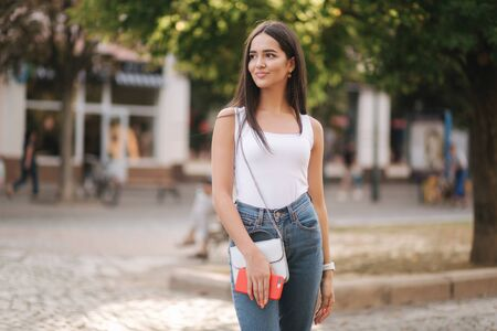 Attractive young woman walking by herself in centre of city in summer time. Woman walk alone. Happy woman outdoors. Social distancing