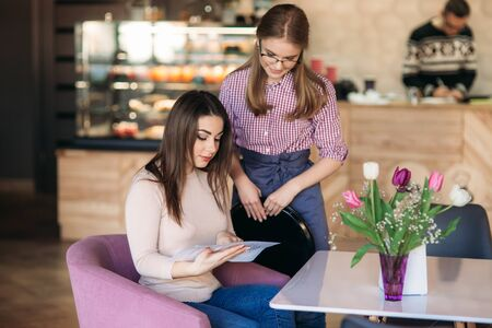 Hospitable waitress help to customer what to choose something from menu