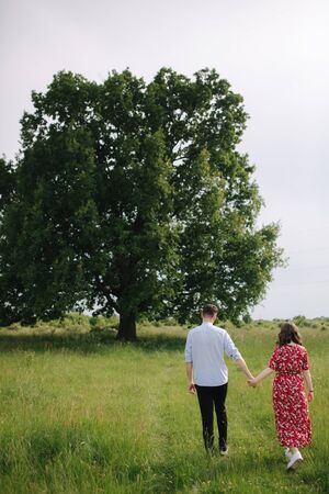Young couple walking in front of big tree. Happpy man and woman spend time toghether. Woman in red dress