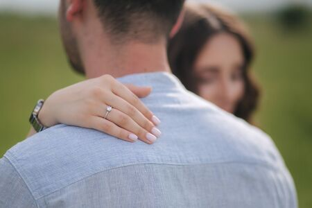 Beautiful woman hug her belowed man. Hand with engagement ring