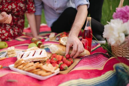 Close up of hand take strawberry on mini picnic outdoors. Man and woman eat outside Archivio Fotografico