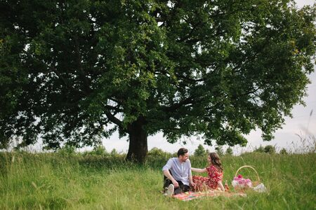 Happy couple sits has mini picnic near the big tree. Non alcoholic picnic