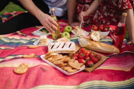 Close up of man and woman has non alcoholic picnic outdoors. Strawberry, lemonade, bread and other snacks Standard-Bild