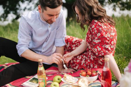 Happy couple spend time outdoors on mini picnic. Attractive woman and handsome man sits on red blanker by the big tree Archivio Fotografico