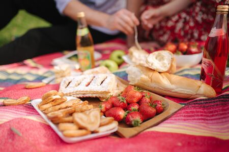 Close up of man and woman has non alcoholic picnic outdoors. Strawberry, lemonade, bread and other snacks Archivio Fotografico