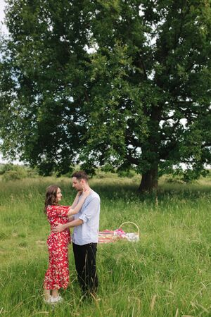 Happy woman with her beloved man has mini picnic near the big tree. Beautiful couple outdoors