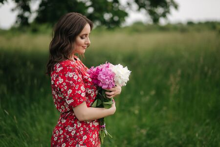 Attractive young woman in red dress with beautiful flowers walking in the field in front of big tree