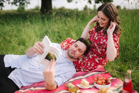 Young couple sits on planket outdoork and read book on mini picnic. Man lies on her knees