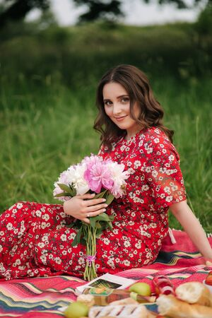 Young woman in red dress sits on red blanket outdoors. Female hold flowers. Mini picninc