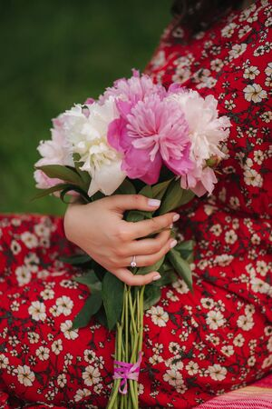 Close up of woman with engagement ring hold bouquet of peony flowers