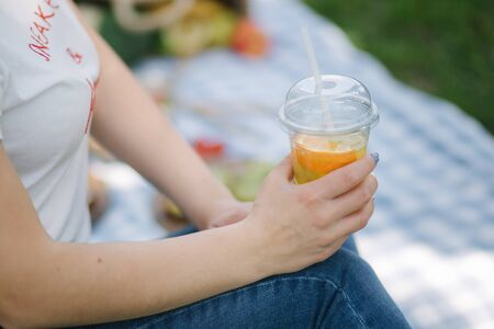 Close-up of woman hold disposable cup with orange lemonade on picnic outdoors. Space for text