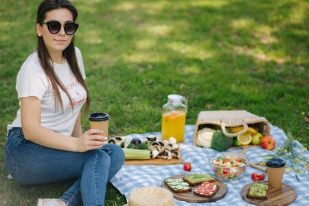Close-up of woman hold disposable cup with coffee on picnic outdoors. Space for text. Vegan picnic concept