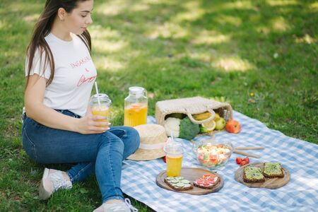 Woman hold disposable cup with orange lemonade on picnic outdoors. Space for text. Vegan picnic concept