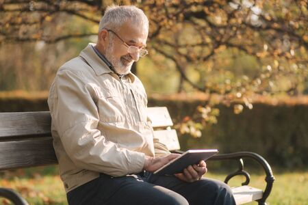 Handsome elderly man sitting on the bench and use tablet for scrolling in internet. Background of autumn tree. 免版税图像