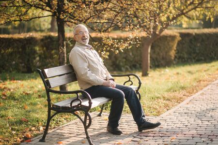 Old gray-haired man rest on the bench in autumn park